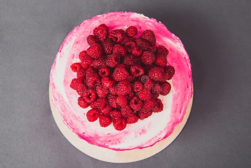 Um bolo delicioso decorado com framboesas em um fundo cinzento imagens de stock
