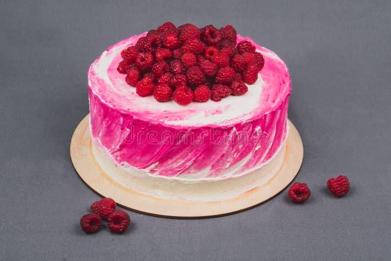Um bolo delicioso decorado com framboesas em um fundo cinzento foto de stock royalty free