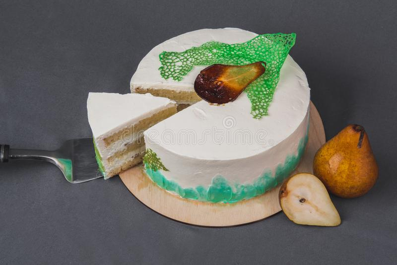Um bolo delicioso decorado com peras caramelizadas em um fundo cinzento fotografia de stock