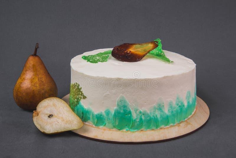 Um bolo delicioso decorado com peras caramelizadas em um fundo cinzento foto de stock royalty free