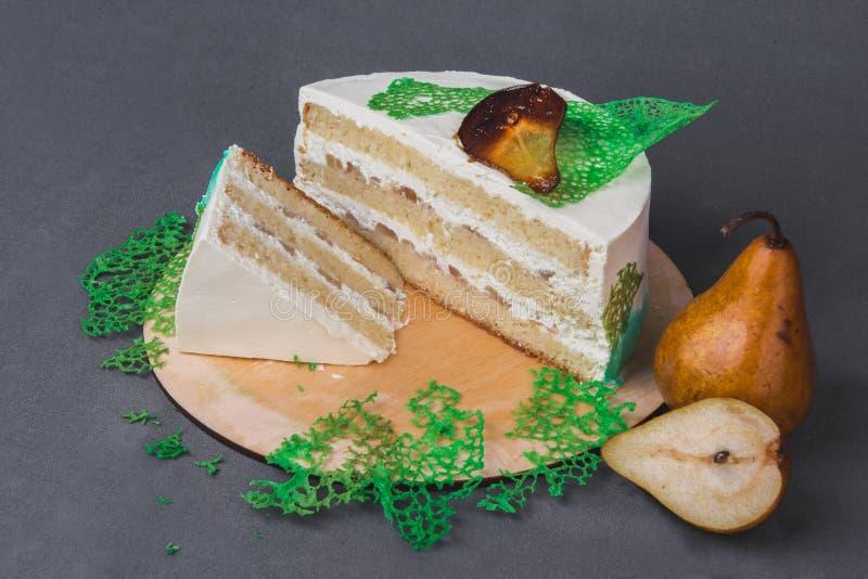 Um bolo delicioso decorado com peras caramelizadas em um fundo cinzento fotos de stock