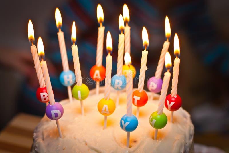 Um bolo e são as velas que lê o feliz aniversario imagem de stock royalty free