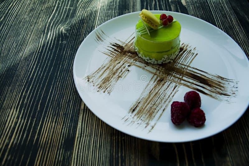 Um bolo pequeno do pistache com um revestimento verde e decorado com viburnum, molho dos confeitos em um fundo preto Vista latera imagem de stock royalty free
