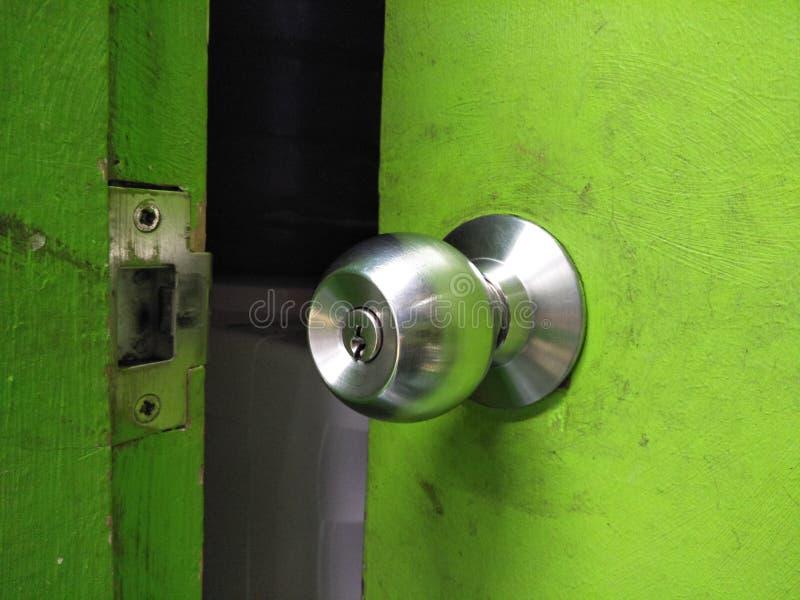 Um botão em uma porta verde imagens de stock