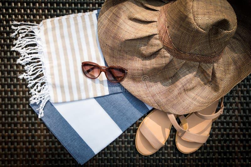 Um branco, uma toalha turca azul e bege, uns óculos de sol, umas sandálias de couro bege das senhoras e um chapéu de palha em um  foto de stock royalty free