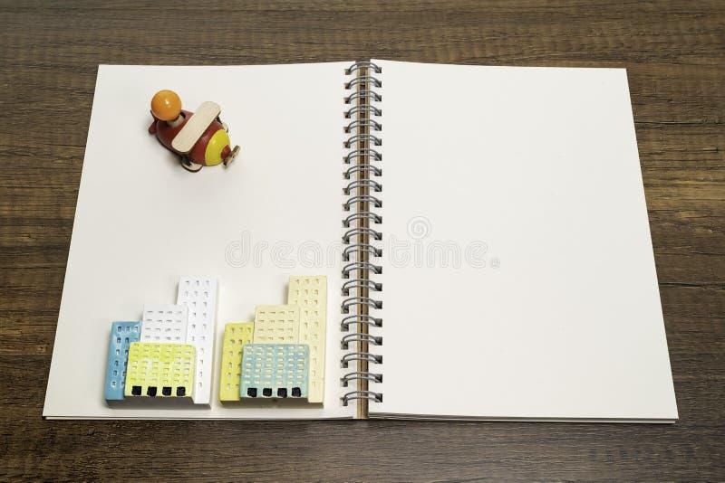 Um brinquedo de madeira vermelho e amarelo do avião no caderno branco vazio com duas construções cerâmicas foto de stock