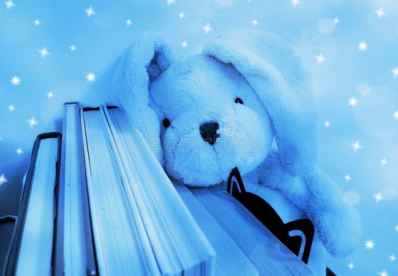 Um brinquedo do luxuoso do coelho descansa sua cabeça em uma fileira dos livros Bokeh e efeito tonificados, macios azuis da estre imagens de stock royalty free