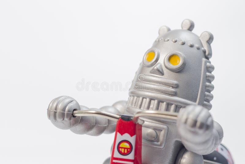 Um brinquedo do robô está montando a bicicleta fotos de stock royalty free