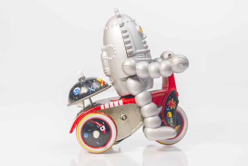Um brinquedo do robô está montando a bicicleta foto de stock royalty free