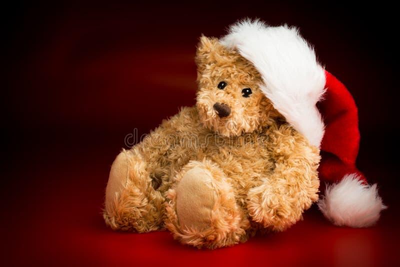 Um Brown Teddy Bear Wearing um chapéu do Natal imagens de stock royalty free