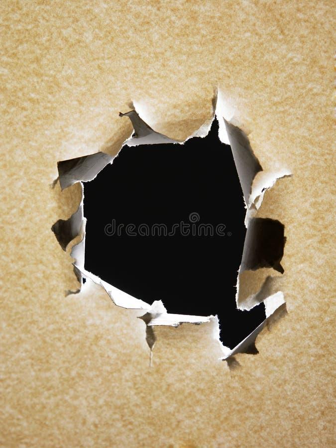 Um buraco de bala no papel imagem de stock