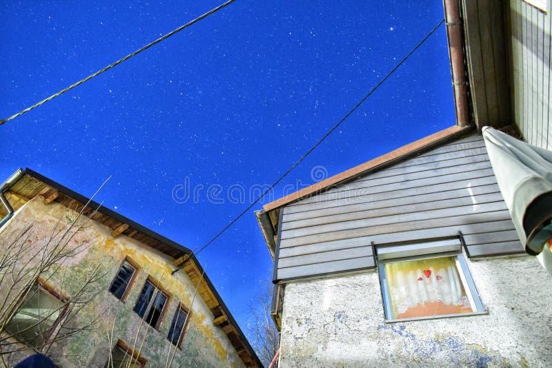 Um céu completamente das estrelas entre casas velhas imagens de stock
