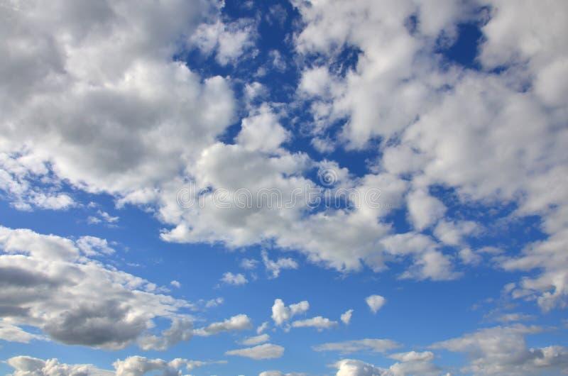 Um céu nebuloso azul com muitas nuvens pequenas que obstruem a SU foto de stock royalty free