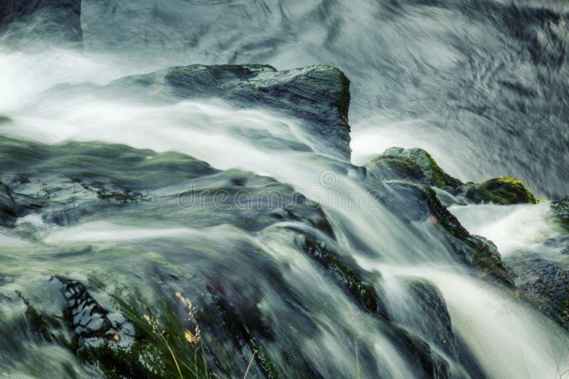 Um córrego poderoso da água entre as pedras imagens de stock royalty free