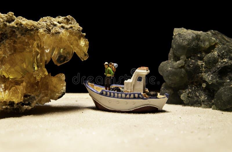 Um caçador de tesouro no barco que olha a pedra de cristal amarela com a pedra verde do jade fotos de stock