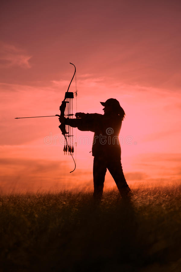 Bowhunter fêmea no por do sol imagem de stock