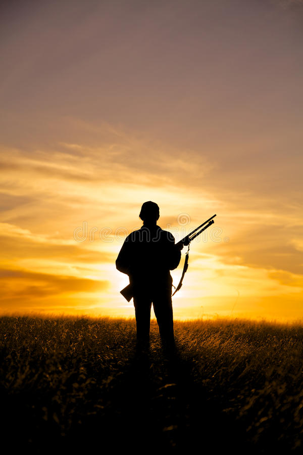 Caçador do rifle no por do sol