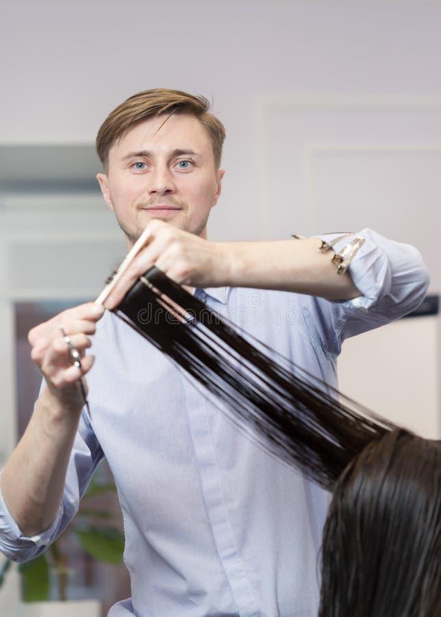 Um cabeleireiro considerável que faz o corte de cabelo para a imagens de stock