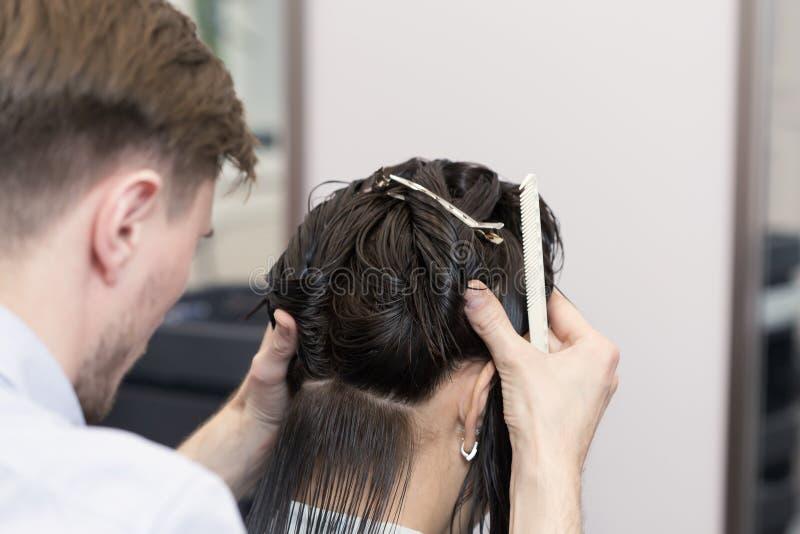 Um cabeleireiro considerável que faz um corte de cabelo para a menina moreno imagens de stock