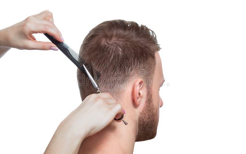 Um cabeleireiro faz um corte de cabelo para um homem novo em um barbeiro foto de stock royalty free