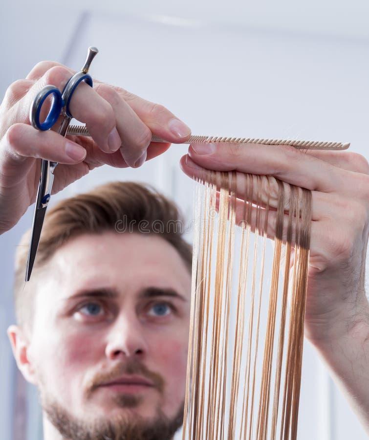 Um cabeleireiro que faz um corte de cabelo para um cliente fêmea louro imagem de stock