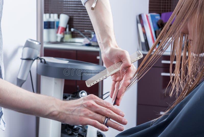 Um cabeleireiro que faz um corte de cabelo para um cliente fêmea louro fotos de stock royalty free