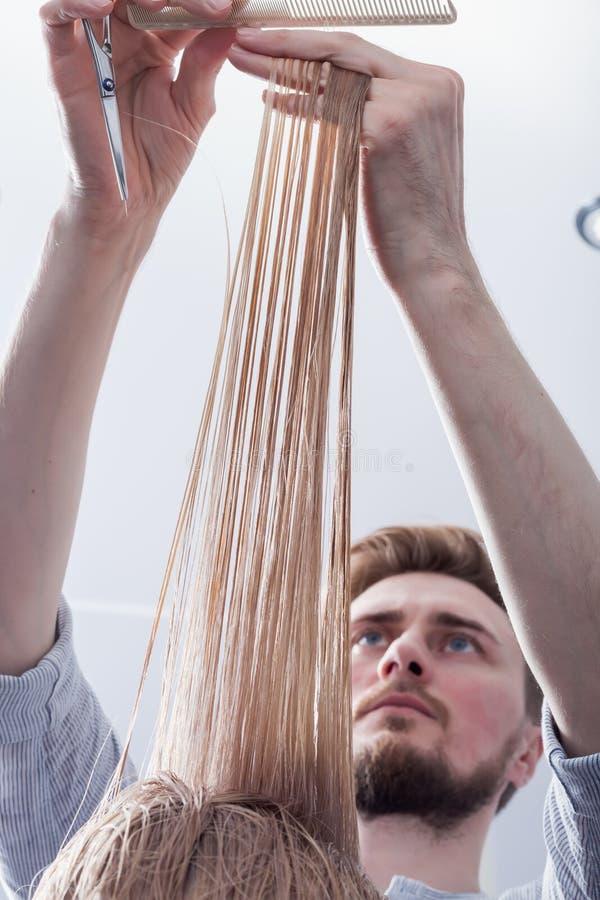 Um cabeleireiro que faz um corte de cabelo para um cliente fêmea louro foto de stock royalty free