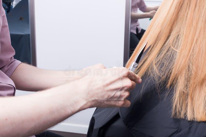 Um cabeleireiro que faz um corte de cabelo para um cliente fêmea louro imagem de stock royalty free