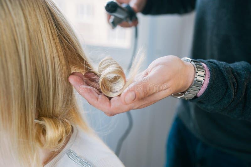 Um cabeleireiro que faz um corte de cabelo para um cliente f?mea louro imagem de stock royalty free