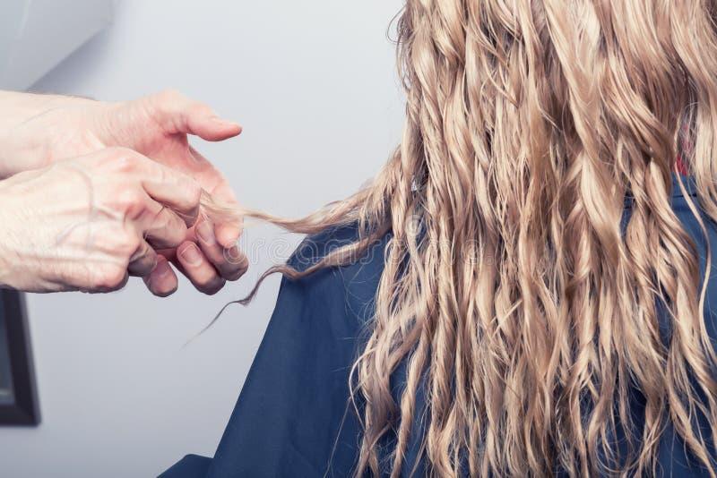 Um cabeleireiro que faz um corte de cabelo para uma menina loura foto de stock