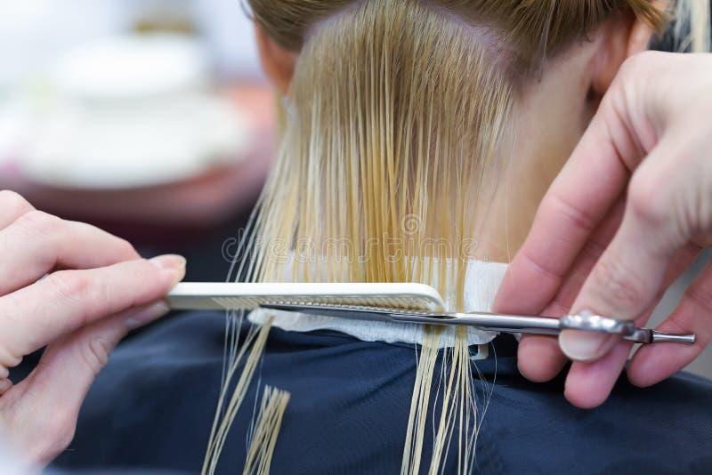 Um cabeleireiro que faz o corte de cabelo para um cliente fêmea louro fotografia de stock royalty free