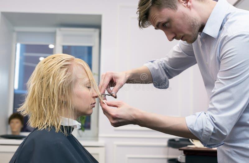 Um cabeleireiro que faz o corte de cabelo para um cliente fêmea louro fotos de stock