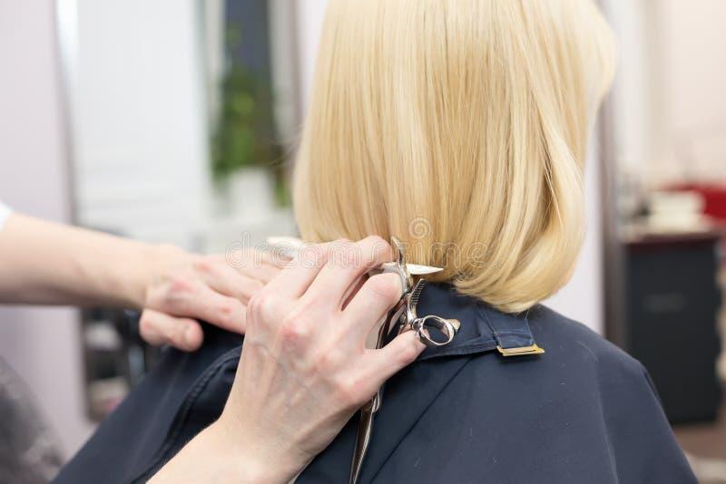 Um cabeleireiro que faz o corte de cabelo para um cliente fêmea louro fotografia de stock