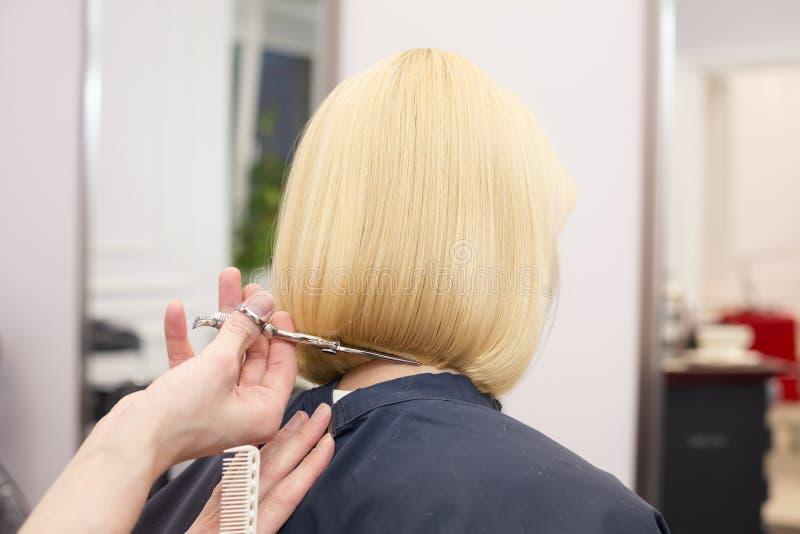 Um cabeleireiro que faz o corte de cabelo para uma fêmea do louro imagens de stock royalty free