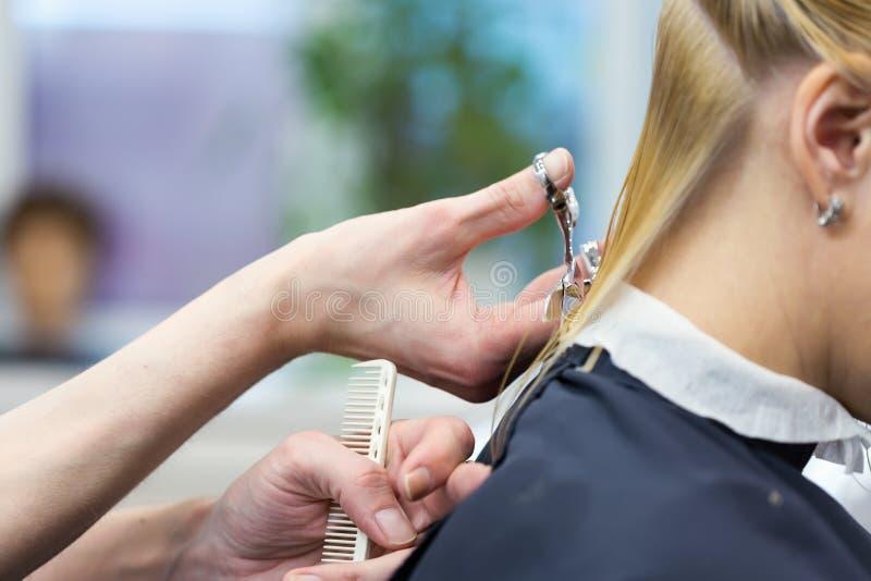 Um cabeleireiro que faz o corte de cabelo para uma fêmea do louro imagem de stock