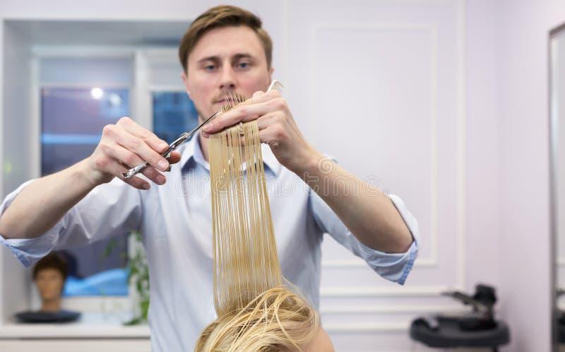 Um cabeleireiro que faz o corte de cabelo para uma fêmea do louro imagens de stock