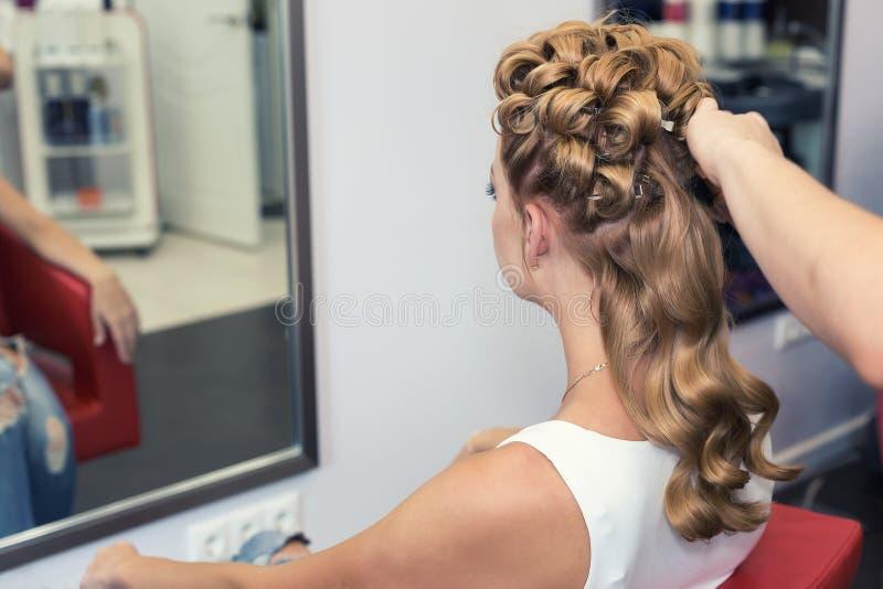 Um cabeleireiro que faz um corte de cabelo para a jovem mulher fotos de stock