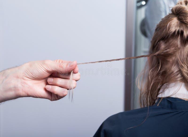 Um cabeleireiro que faz um corte de cabelo para uma menina loura imagens de stock royalty free