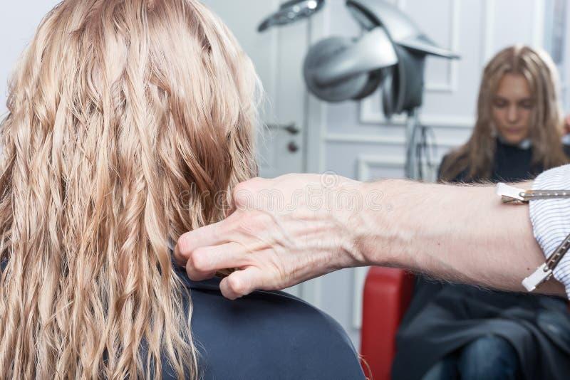 Um cabeleireiro que faz um corte de cabelo para uma menina loura fotografia de stock