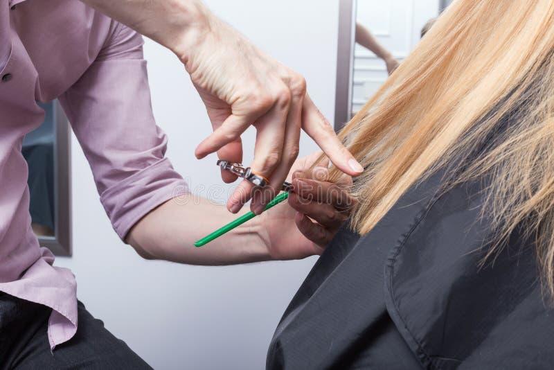 Um cabeleireiro que faz um corte de cabelo para uma menina loura imagens de stock