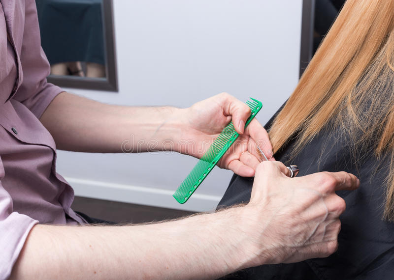 Um cabeleireiro que faz um corte de cabelo para uma menina loura fotos de stock