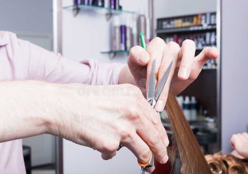 Um cabeleireiro que faz um corte de cabelo para uma menina loura fotografia de stock royalty free