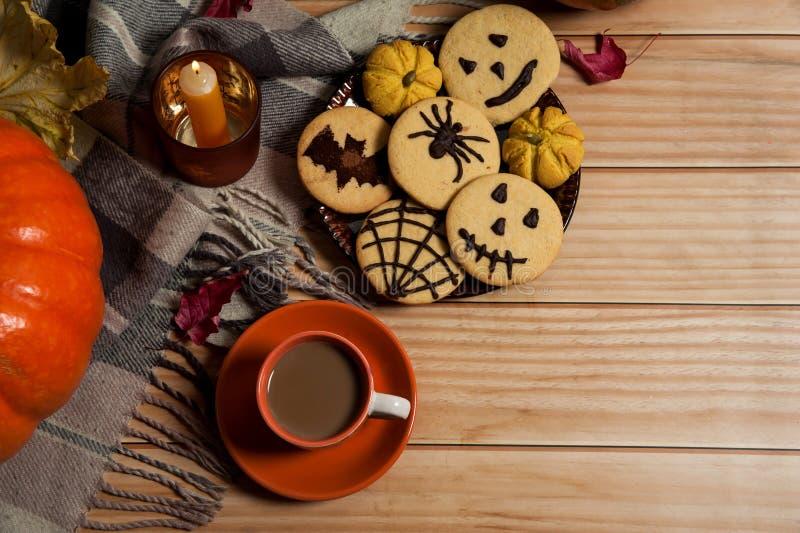 Um cachecol, uma Taça de café com leite, folhas de outono, uma vela, biscoitos caseiros deliciosos com aranhas, morcegos, emotico fotografia de stock royalty free