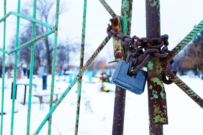 Um cadeado que pendura em uma corrente de portas oxidadas em um cemitério, um cemitério fechado na vila imagens de stock royalty free