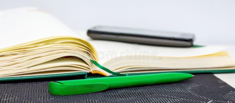 Um caderno aberto com pena e telefone para gravar importante dentro imagens de stock