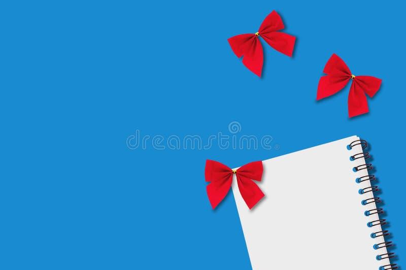 Um caderno de papel vazio com fio espiral e a matéria têxtil três festiva vermelha amarrou curvas na tabela azul copie o espaço p fotografia de stock
