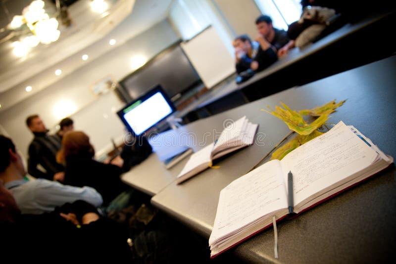Um caderno e uma pena do professor na tabela e os estudantes durante o estudo ou o questionário, o teste e o exame na grande sala foto de stock royalty free