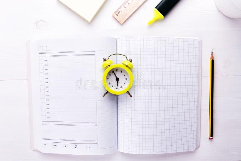 Um caderno-planejador aberto com um despertador no centro em um fundo branco Hora de fazer o negócio, espaço da cópia foto de stock royalty free