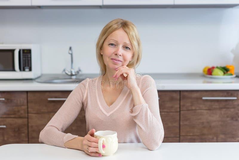Um café bebendo da mulher ativa da Idade Média em casa fotos de stock royalty free