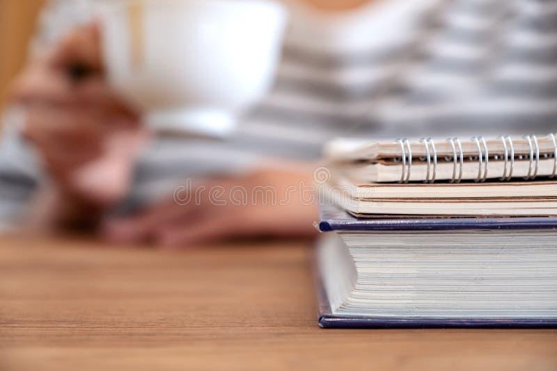 Um café bebendo da mulher com livros e cadernos na tabela de madeira fotografia de stock royalty free